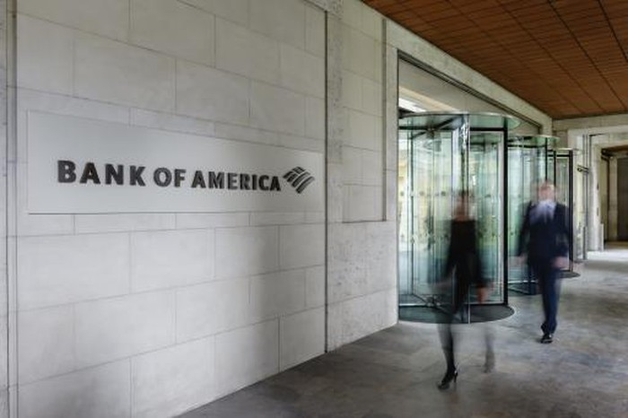 Picture of wall with Bank of America logo and people walking by.