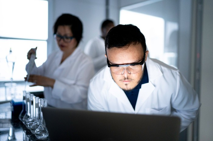 A researcher looks at a computer in a lab while others conduct research in the background.