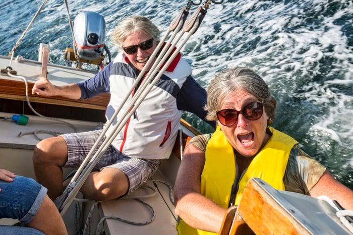 Un homme et une femme dans un voilier réagissent lorsque le bateau bascule sur le côté.