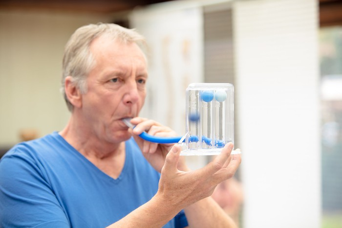 A patient testing their lung capacity at a doctor's office.