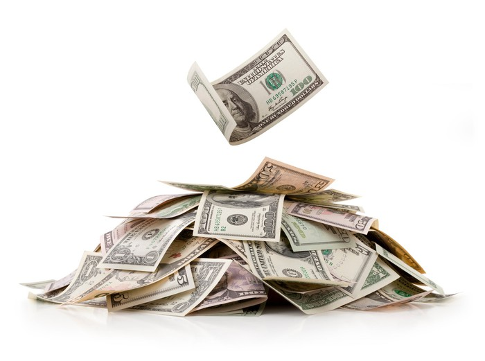 A pile of loose money in all denominations, with a one hundred dollar bill floating above it.