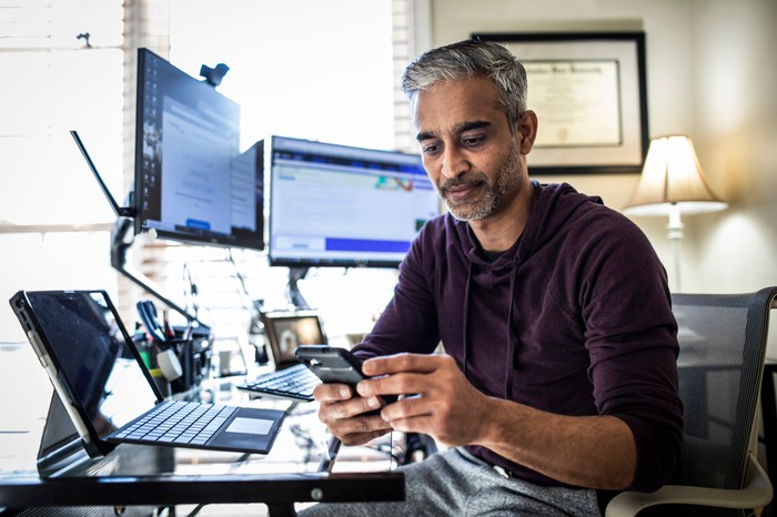 Someone in a home office looking at a smartphone with two monitors behind him and an open laptop.