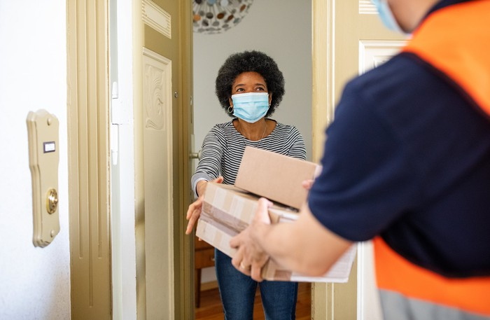 A person receiving a package with a mask on.