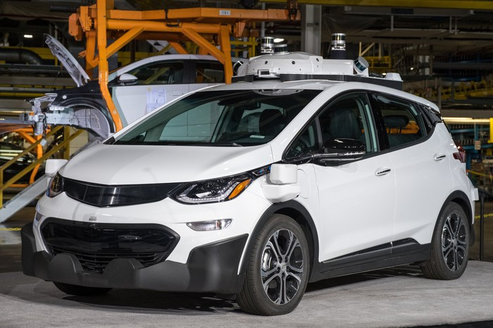 A white Chevy Bolt autonomous vehicle, with other AVs being built in the background.