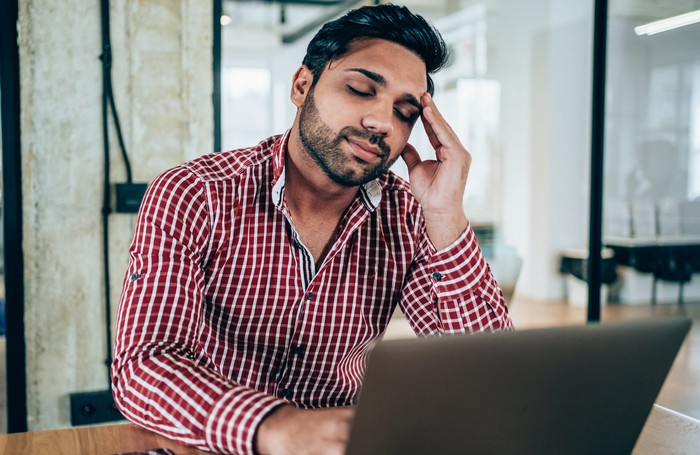 Disappointed investor in front of computer.