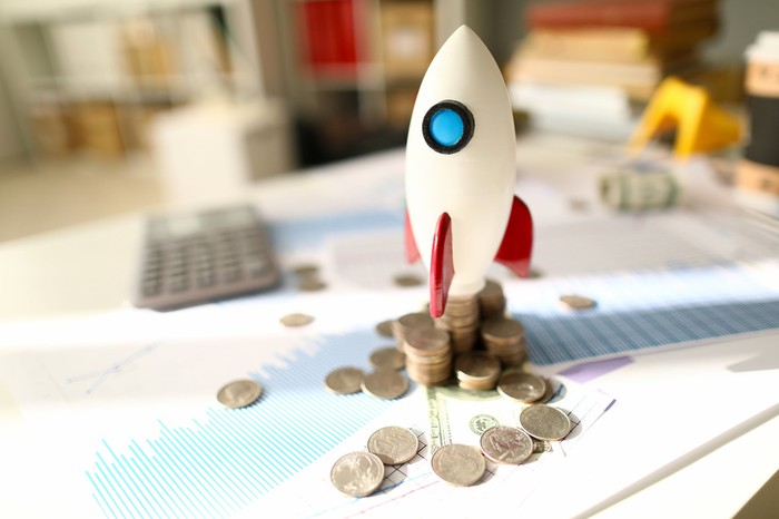 A white rocket set atop a messy pile of coins and paperwork displaying financial metrics.
