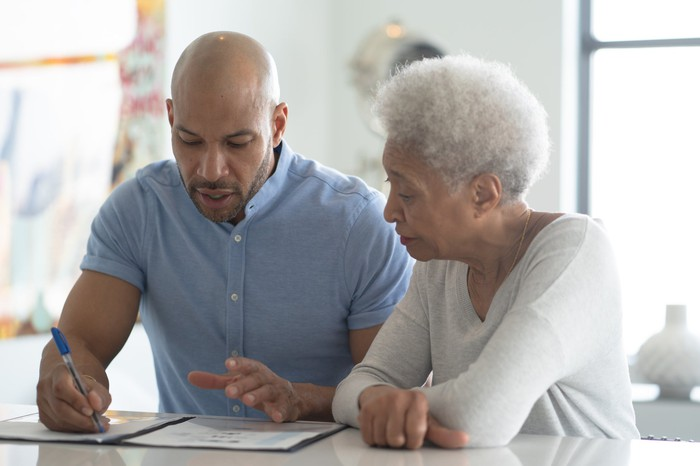 Older couple sitting at a desk looking at documents