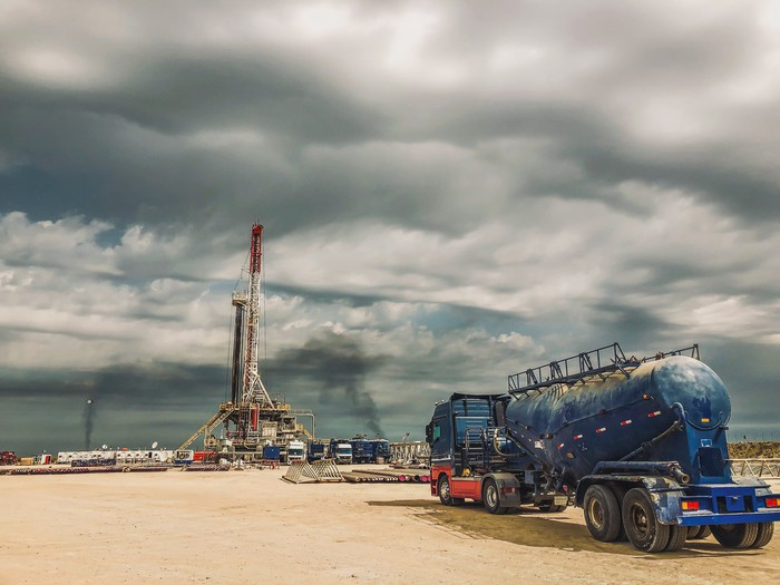 Shale rig with tanker in foreground.