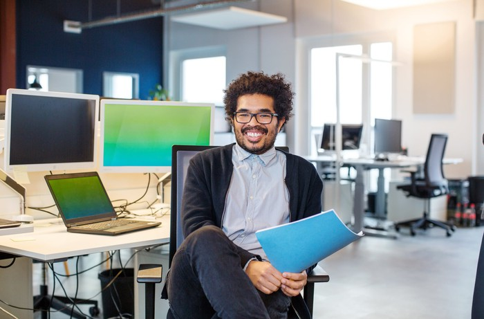 Smiling person at desk holding file.