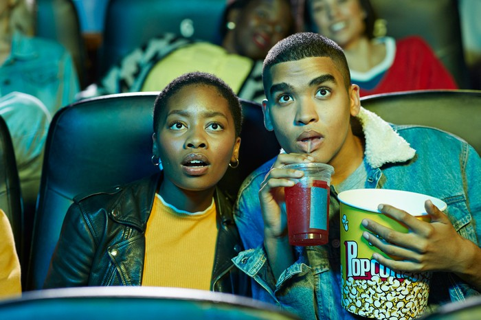 A couple watch a movie in a crowded theater as they enjoy popcorn and a beverage.