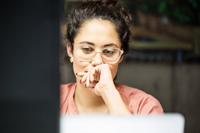 A young businesswoman thinking something while looking at a computer.