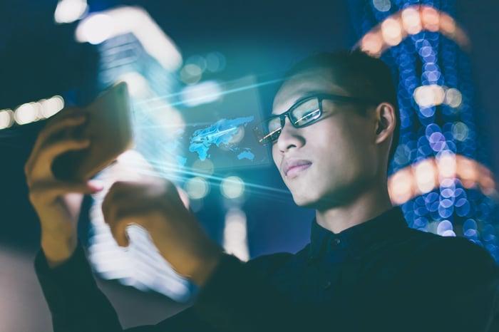 Un homme regardant un smartphone avec des lumières floues en arrière-plan