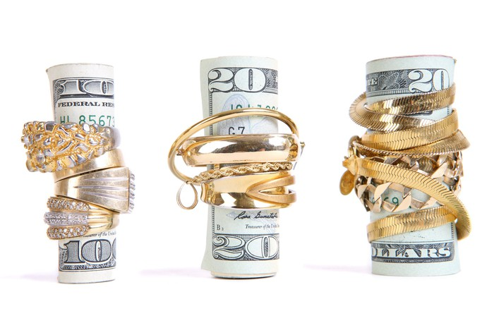 A $100 bill and two $20 bills, each wrapped up tightly in gold jewelry, on a white background.