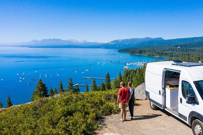 Two people standing next to RV on scenic overlook above Lake Tahoe.