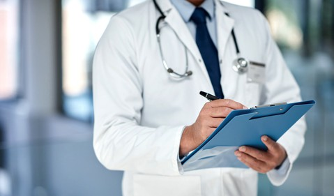 A doctor writing in a patients medical record