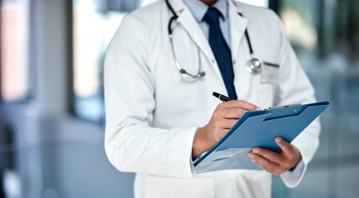 A doctor writing in a patients medical record.
