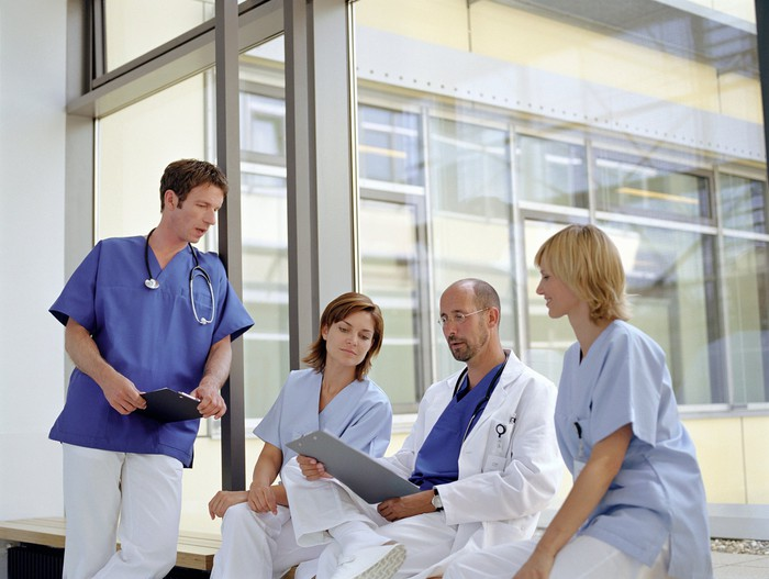 Doctors and nurses looking at a patient chart and talking near a hospital window.