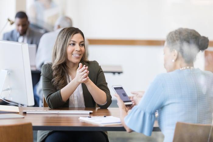 Pessoa sorridente do outro lado da mesa do cliente segurando o smartphone com o aplicativo em execução.