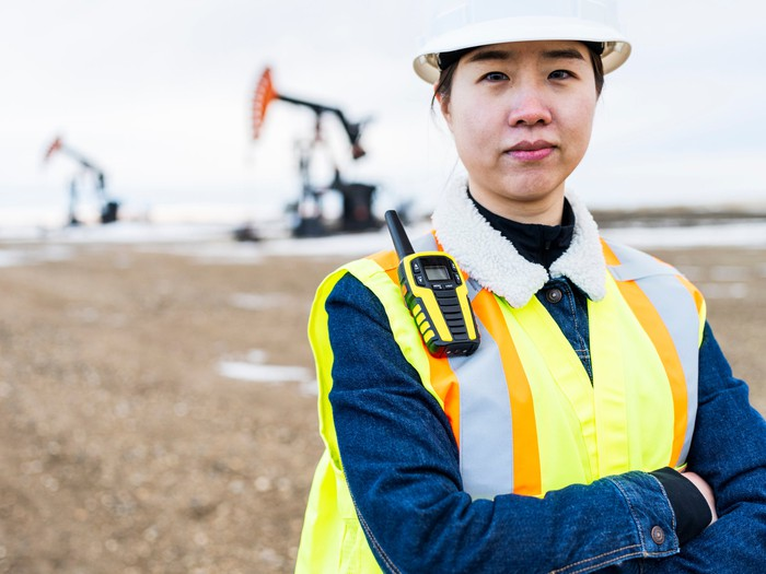 A person in protective gear with oil wells in the background.
