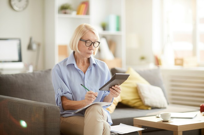 Older person sitting on a couch looking at a calculator