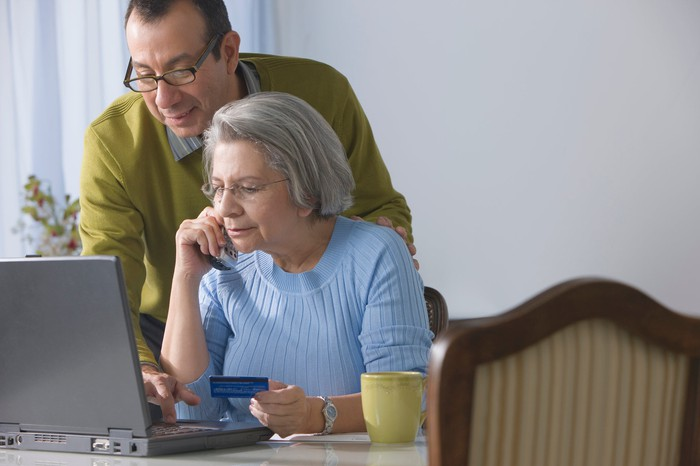 Older couple staring at a laptop at their dining room table while as one of them holds a credit card.