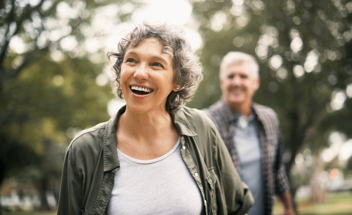 A happy senior couple walking in a park.