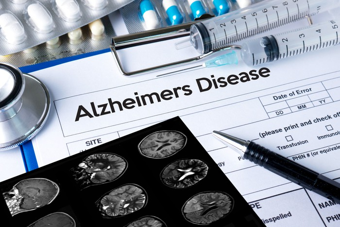 Alzheimer's Disease printed at the top of a form that's next to X-ray images, a pen, syringes, and pills.