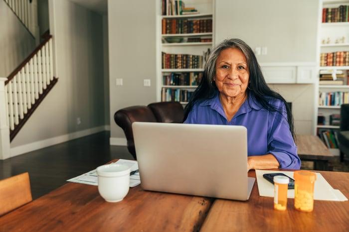 Smiling senior at home laptop.