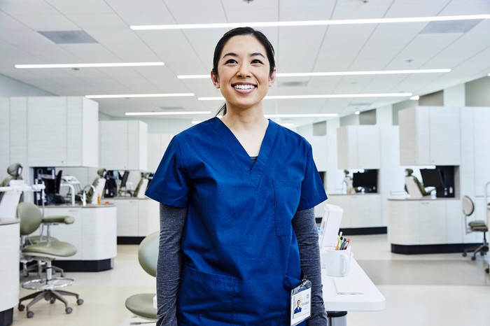 A woman in medical scrubs in a professional setting.