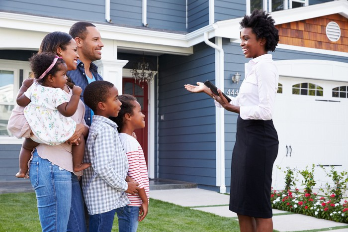 A realtor showing the outside of a home to a family of five.