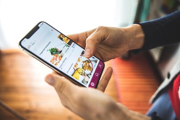 Gros plan du smartphone ouvert à une application de livraison de nourriture.
