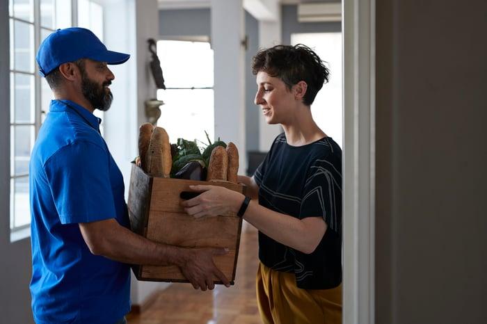 Le livreur donne une boîte d'épicerie à une personne souriante.