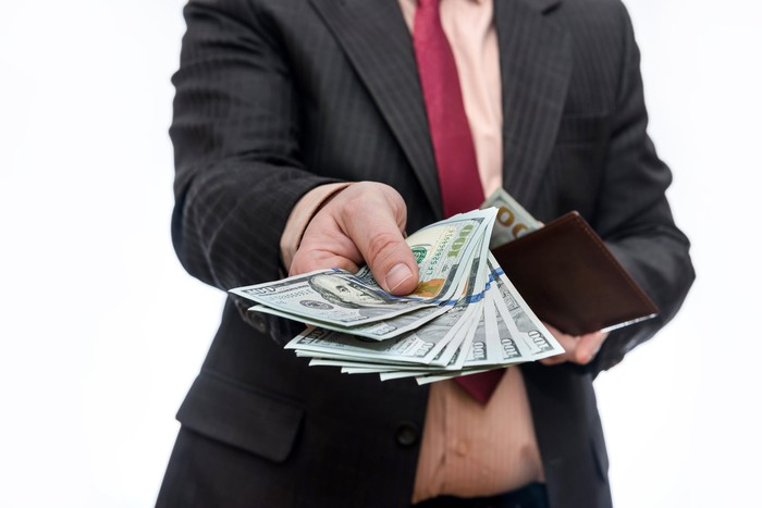 An investor holds out a handful of one hundred dollar bills.