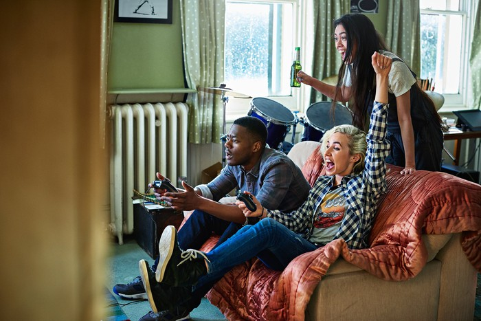 three people in an apartment playing video games and cheering.