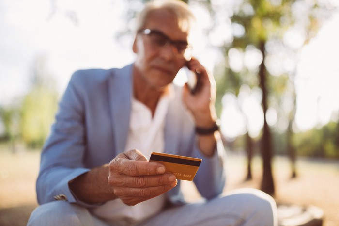 A person talking on the phone while holding a credit card.