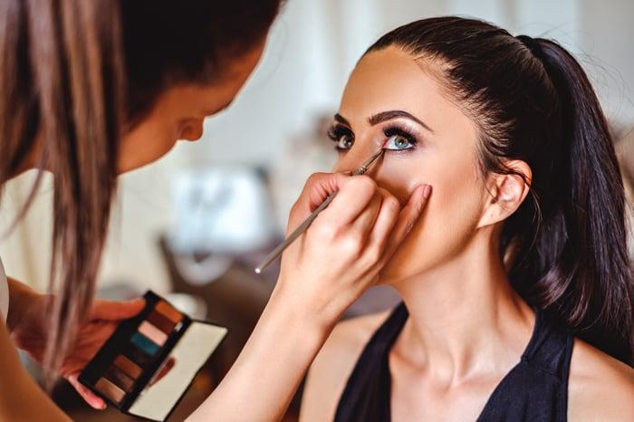 An esthetician applies eye makeup to a client.