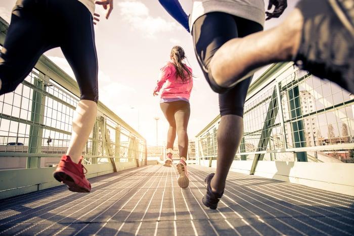 Three people in athleticwear running across a bridge