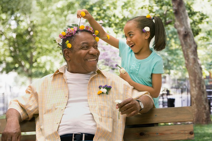 An older person seated on a bench with flowers in their hair, enjoying time spent with the child putting them there.