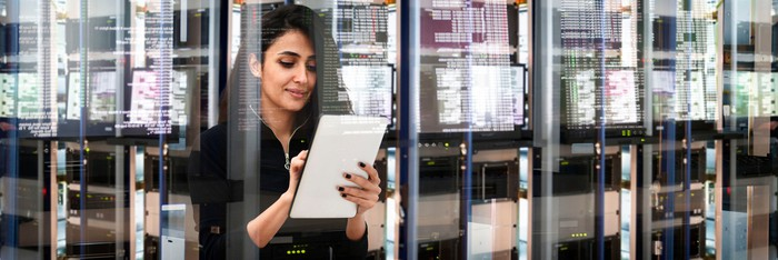 IT professional looking at a document in a data center.
