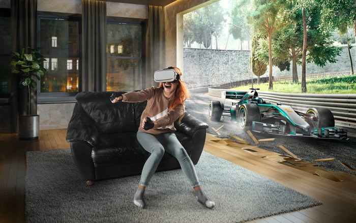 A person wearing a VR headset in a living room, with a racecar in the background representing the gaming experience they see.
