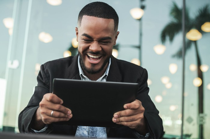 A man in casual gear holds a tablet and smiles in reaction to something on it.