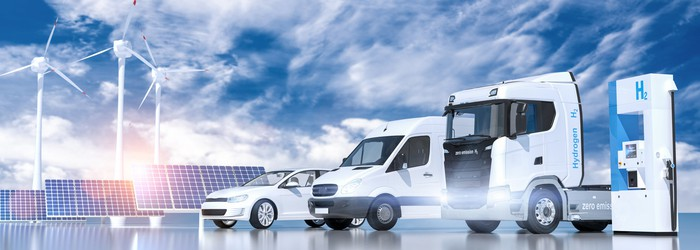 A hydrogen refueling station with two white trucks and a white car. Solar panels and wind turbines are in the background.