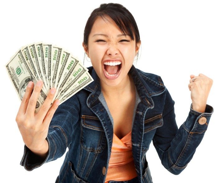 A person holding several $100 bills cheers from the windfall.