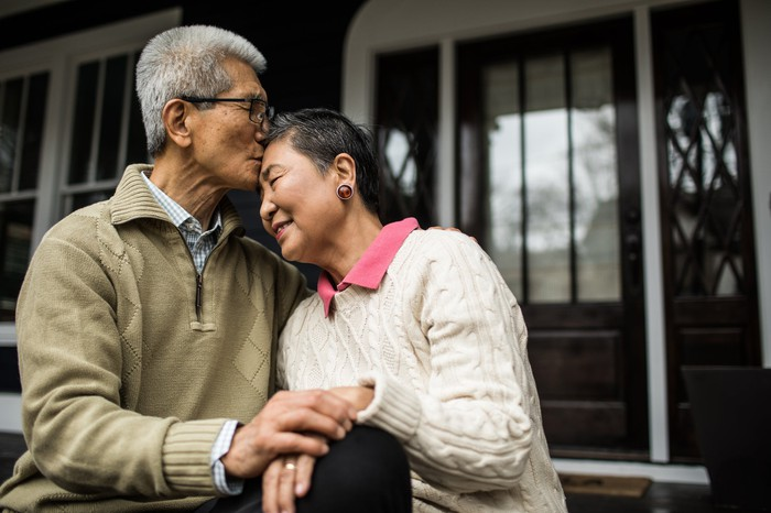 Two older people embracing in front of a house.