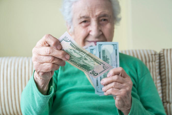 Older person holding $50 and $100 bills.