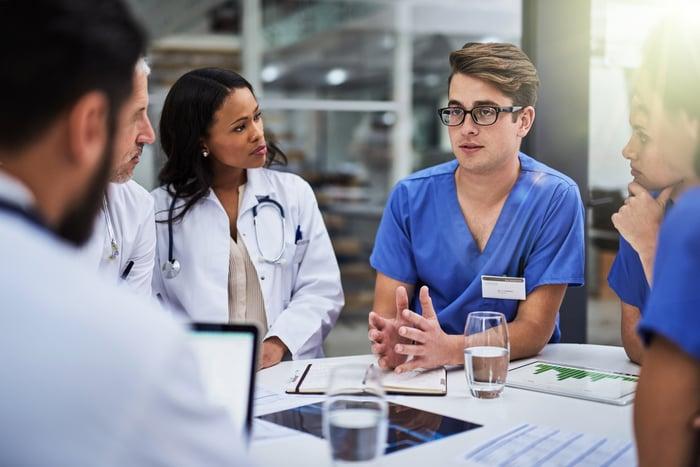 Une infirmière discute de son point de vue sur une impression de données alors qu'elle est assise à une table avec plusieurs autres médecins et infirmières.