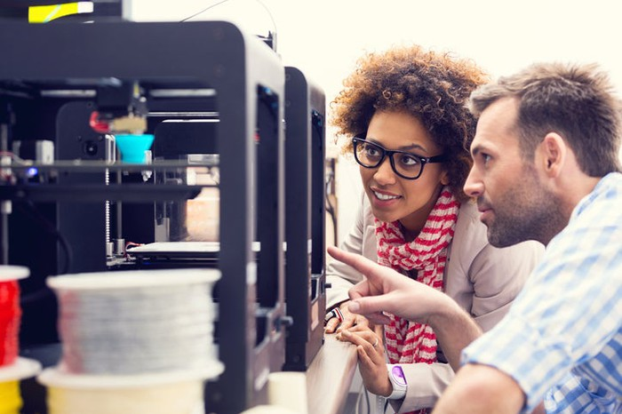 Two people watch a 3D printer build a new object.