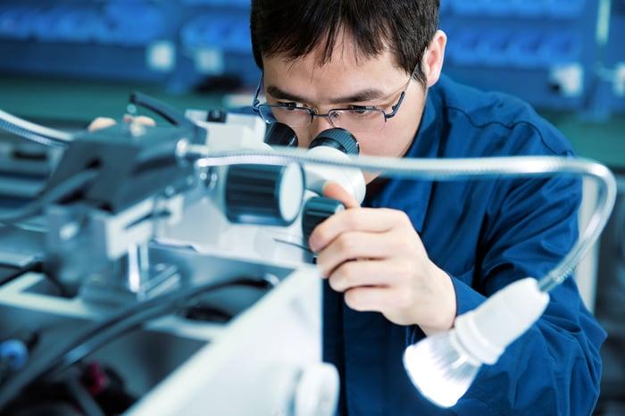 Un technicien examine un semi-conducteur au microscope.