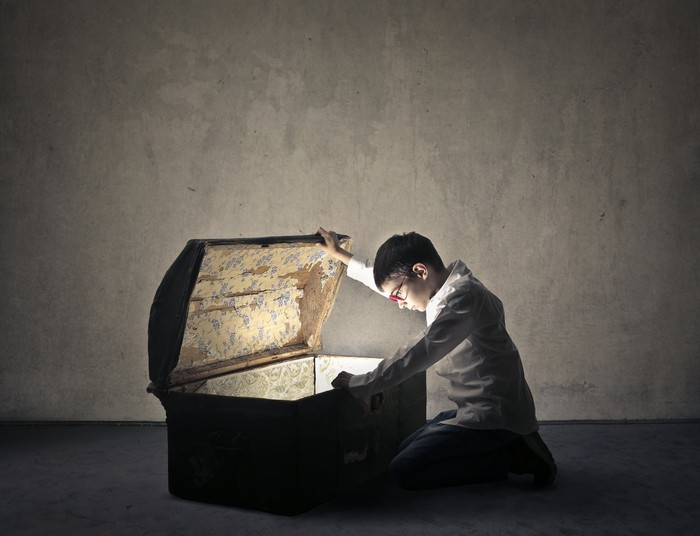 Person looking inside a treasure chest.
