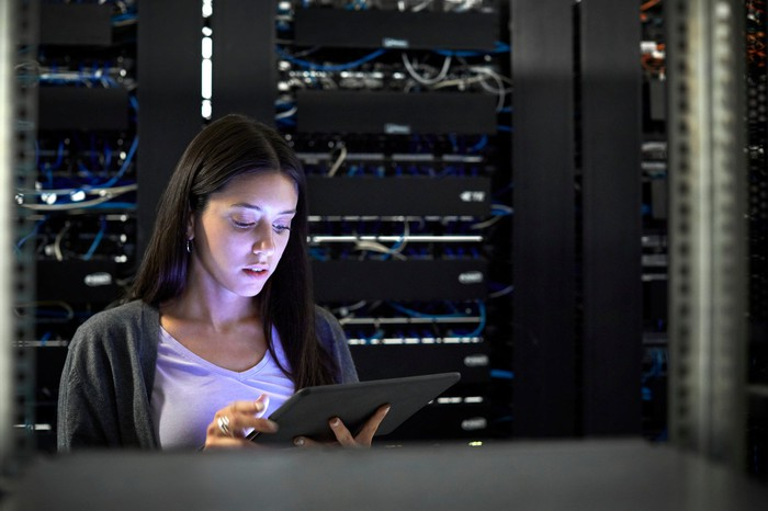A woman on a tablet in a server room